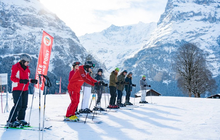 tour goers watching their guide while prepping to ski