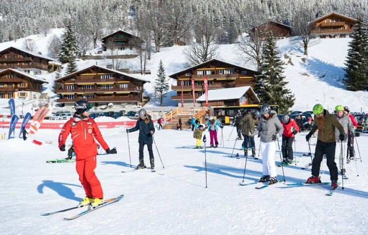 beginners watching guide teach them the basics of skiing