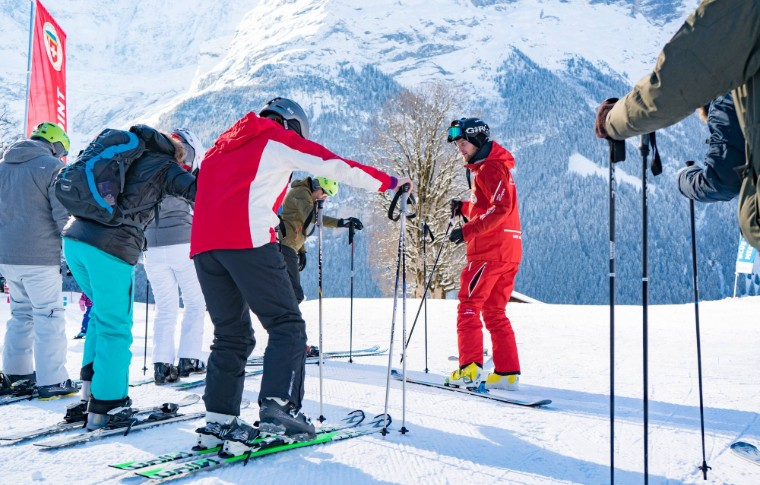 guide making sure his students have the correct gear and position of skis