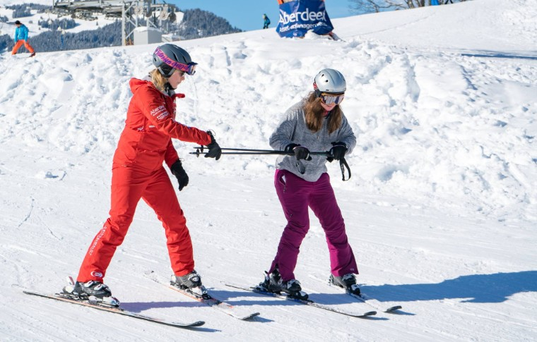 guide teaching a student how to slow down with skis in the snow