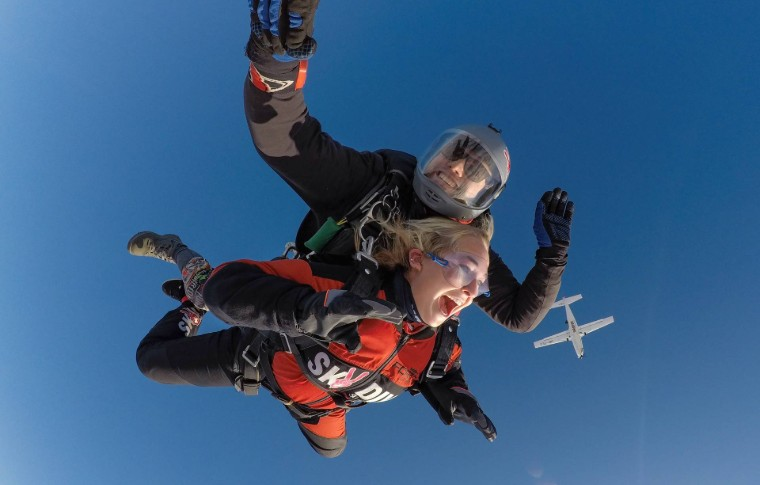 tour goer and guide skydiving in the air with a plane in the background