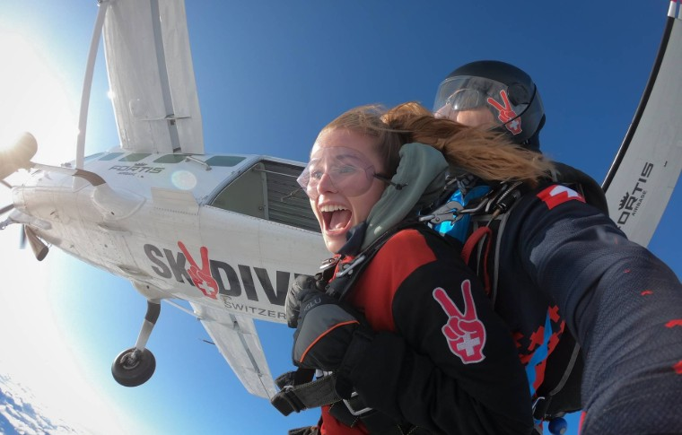 tour goer and guide jumping off the plane to start skydiving