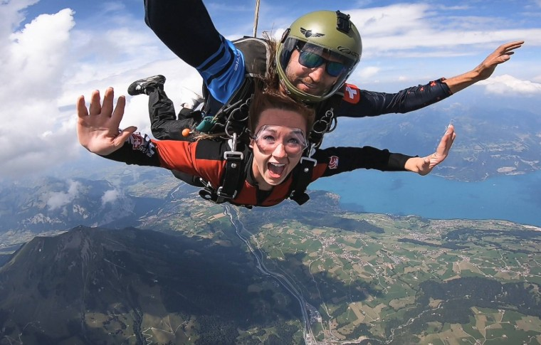 tour goer and guide skydiving in the air with the swiss landscape below them