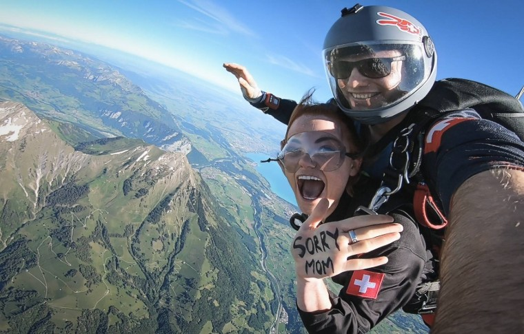 tour goer and guide doing skydiving while handing out her hand to the camera with a message saying 'Sorry Mom'