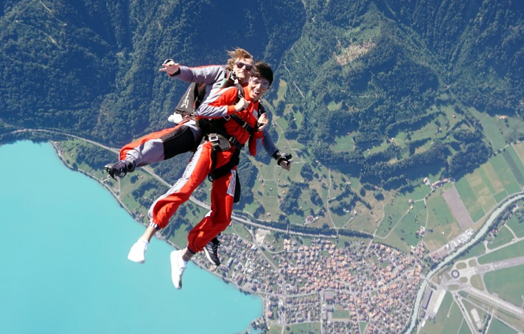 tour goer and guide skydiving with the landscape from the air behind them
