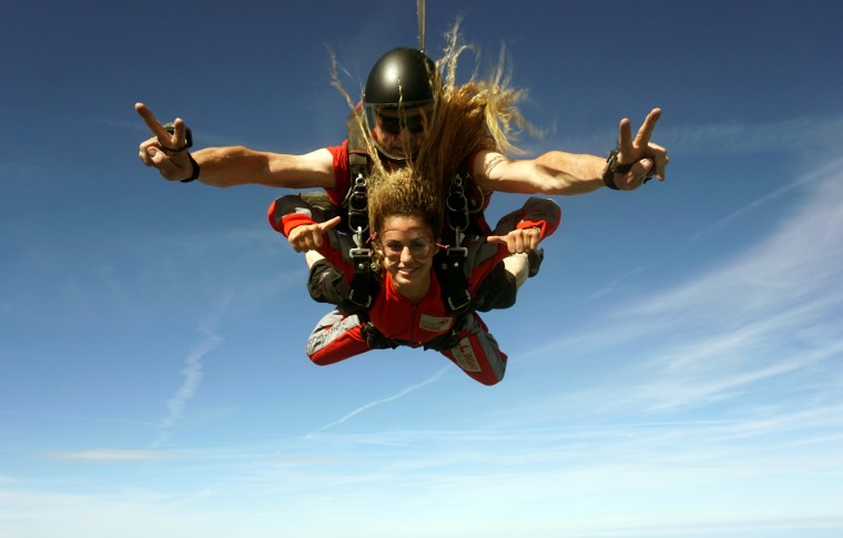 guide and tour goer skydiving with her hair blowing in the wind