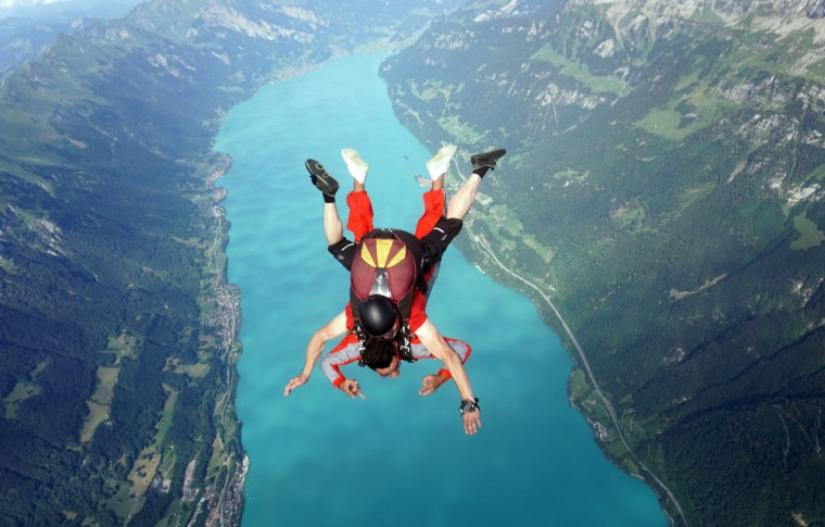 tour goer and guide skydiving over the beautiful swiss lake