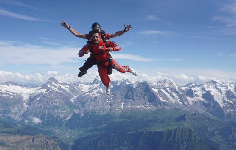 tour goer and guide skydiving with the swiss alps behind them