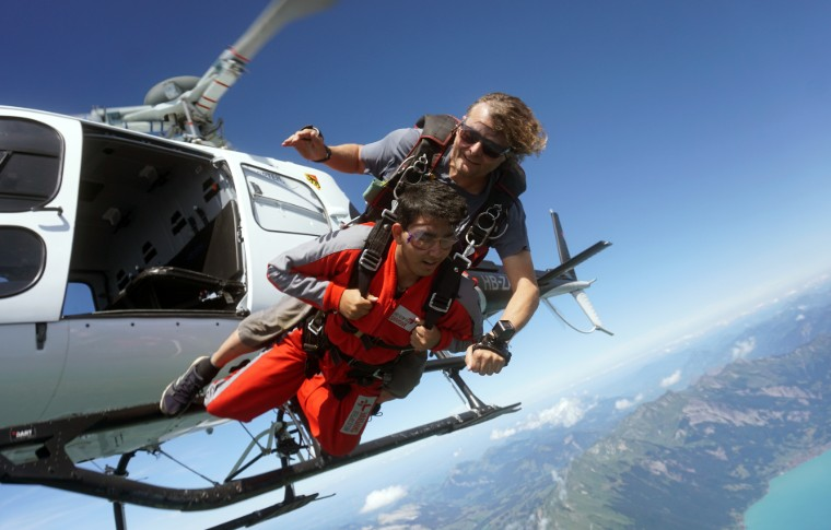 tour goer and guide jumping off the helicopter to start skydiving
