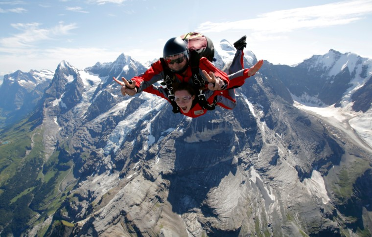 tour goer and guide skydiving with the amazing snowy mountains in the background