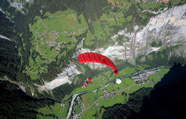 parachute in the air with the beautiful landscape of Switzerland below them