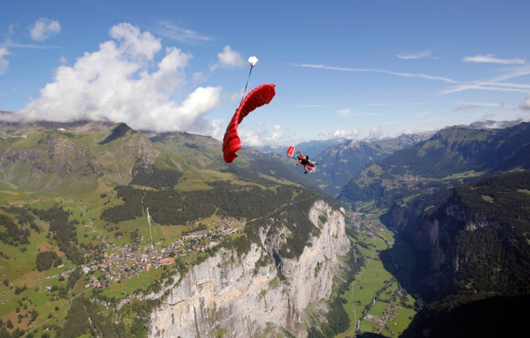 parachute with guide and tour goer flying down the mountains
