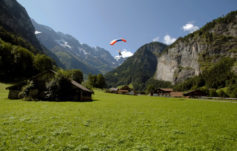 parachute with the guide and tour goer almost landing on the green grass field