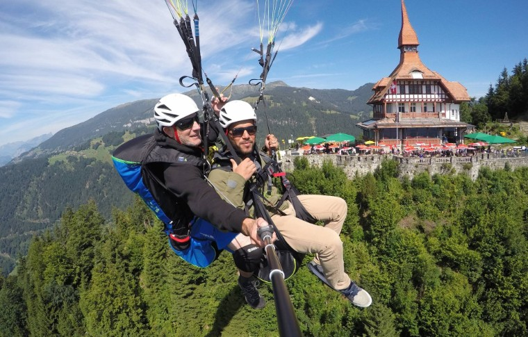 guide and tour goer paragliding over the swiss alpes