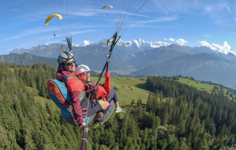 guide and tour goer paragliding over the woods of Switzerland