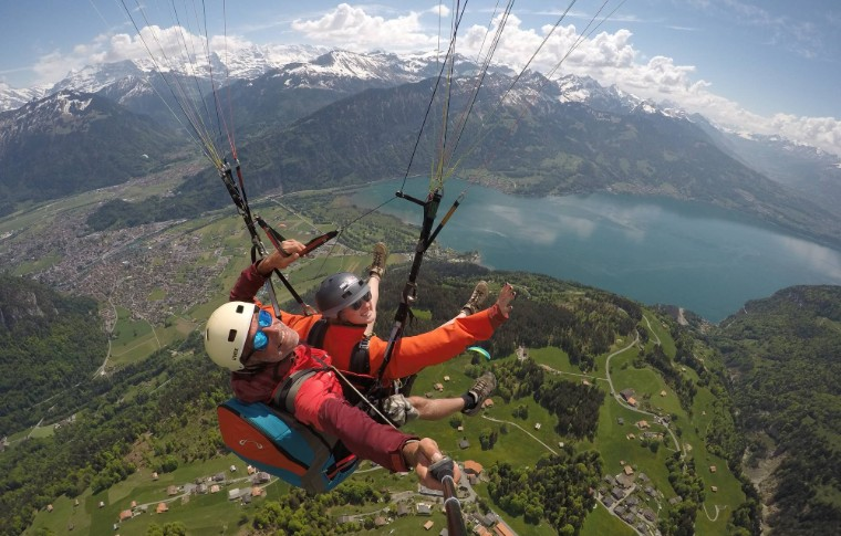 guide and tour goer paragliding over the fields near a lake in Switzerland