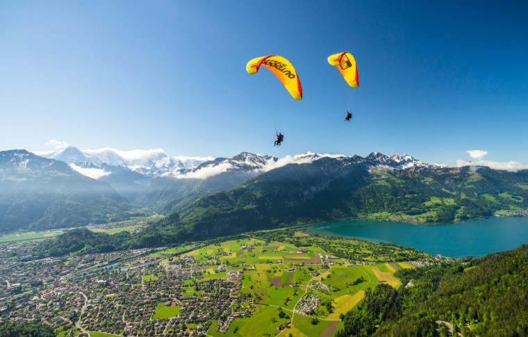 paraglides in summer with the fields and mountain scenery below them