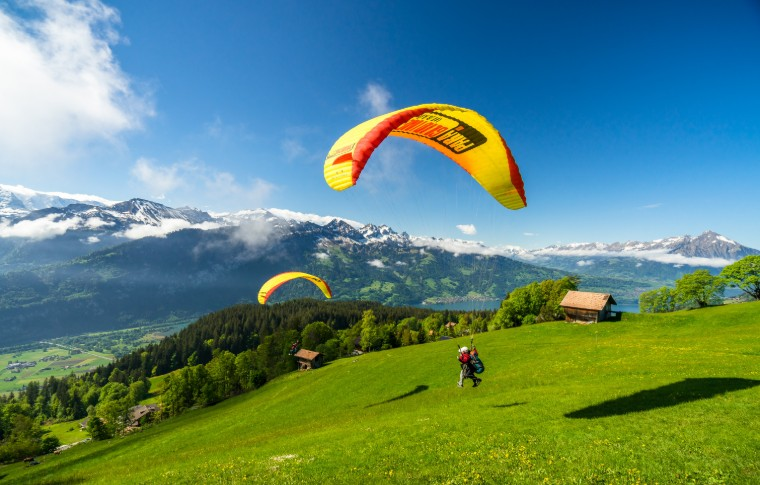 people paragliding almost landing in a green field