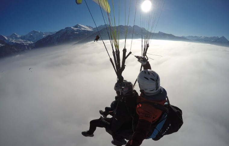 guide and tour goer paragliding over a foggy landscape