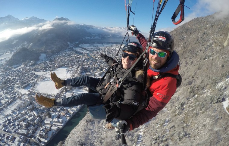 guide and tour goer paragliding over the swiss winter landscape