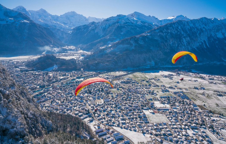 paraglides over the wintery landscape of Switzerland