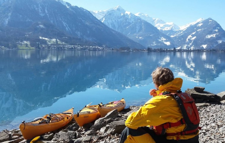 guide watching from the lake shore with some kayaks appreciating the wintery landscape
