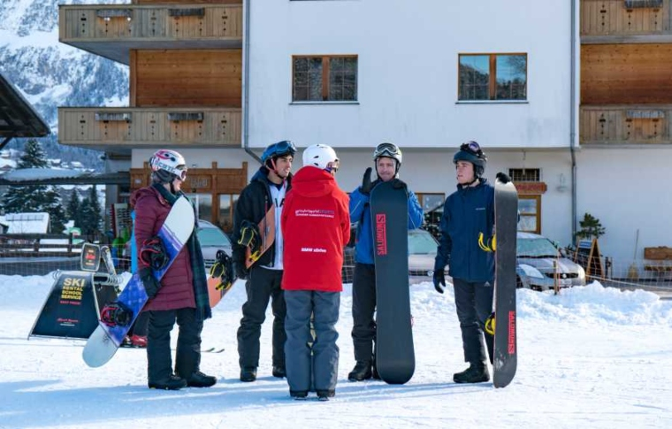 A group of guests in snowboarding clothes talking to one another