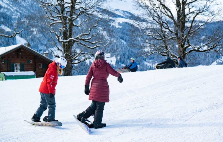 two girls learning snowboarding