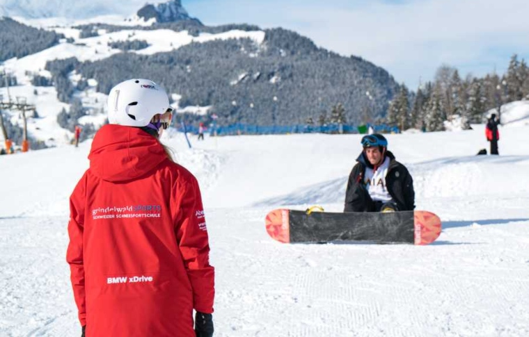 a snowboarding instructor showing a technique to a girl
