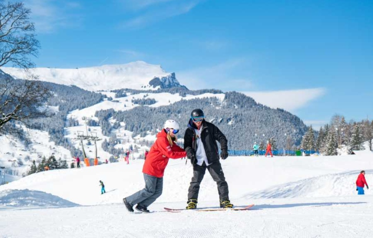 a snowboarding instructor pushing a young man to help him slide