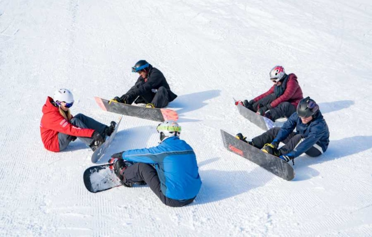 four people with snowboards listening to their instructor and checking their equipment